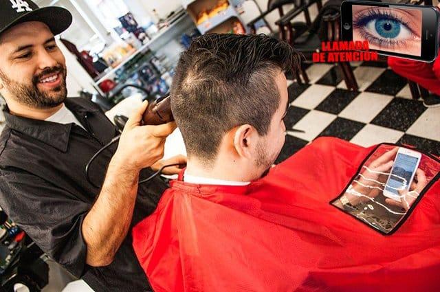El creador de la capa Alejandro Rodriguez realizando el corte de pelo a uno de sus clientes.